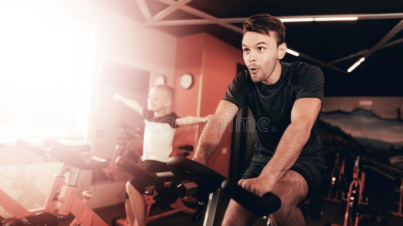 Father And Son Training On Bike Trail In The Gym. royalty free stock photos