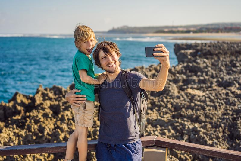 Father and son travelers on amazing Nusadua, Waterbloom Fountain, Bali Island Indonesia. Traveling with kids concept.  royalty free stock image