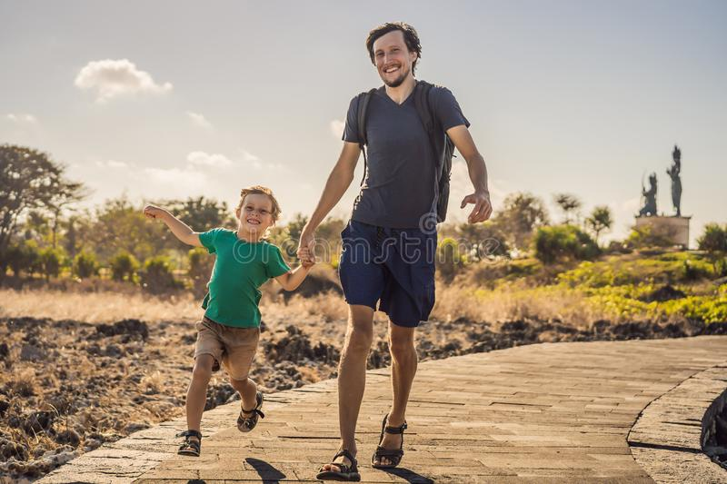 Father and son travelers on amazing Nusadua, Waterbloom Fountain, Bali Island Indonesia. Traveling with kids concept.  stock photo