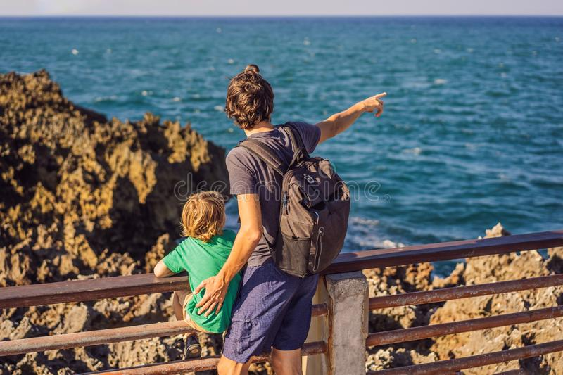 Father and son travelers on amazing Nusadua, Waterbloom Fountain, Bali Island Indonesia. Traveling with kids concept.  royalty free stock photography