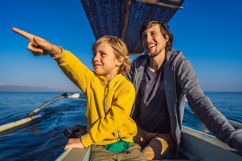 Father and son travelers meets dawn in the sea on a boat.  stock images