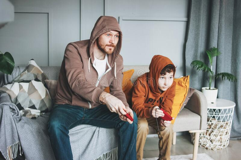 Father and son tween boy in hoodies playing computer games with joystick at home tipical caucasian family. Father and son tween boy in hoodies playing computer royalty free stock photo