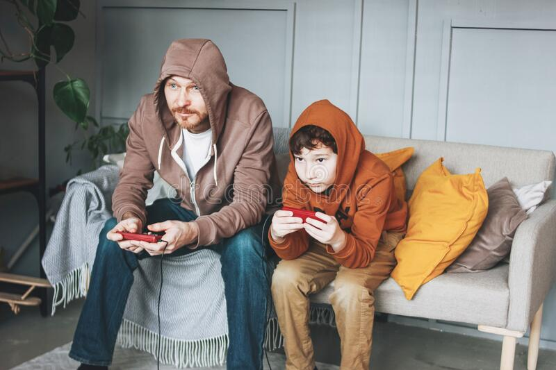 Father and son tween boy in hoodies playing computer games with joystick at home tipical caucasian family. Father and son tween boy in hoodies playing computer royalty free stock photography