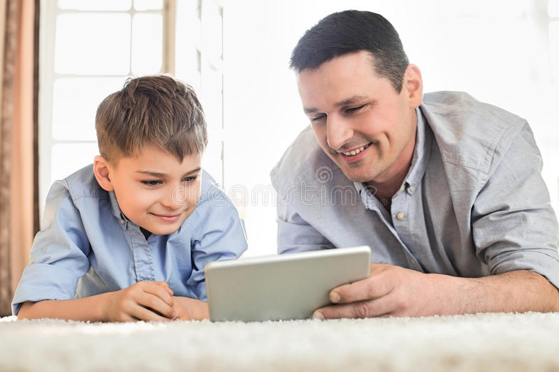 Father and son using digital table on floor at home royalty free stock photo