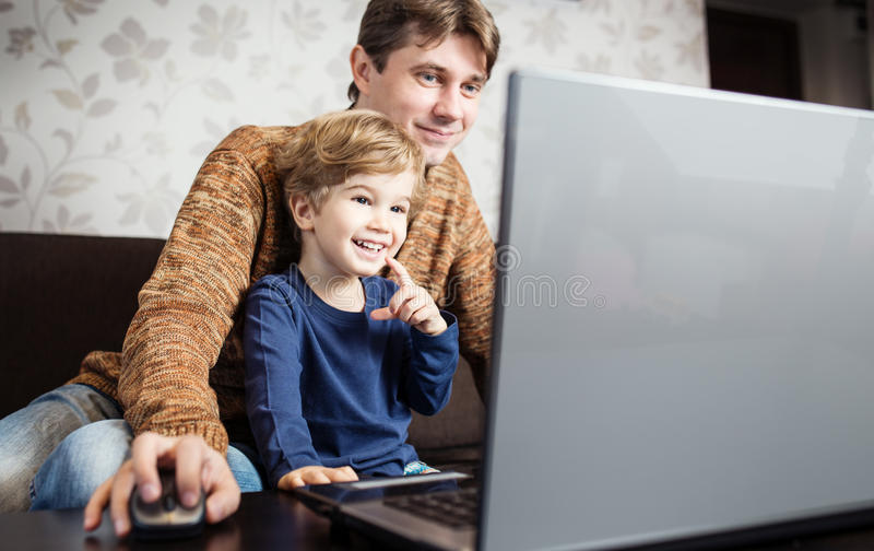 Father and son using laptop on sofa royalty free stock photos