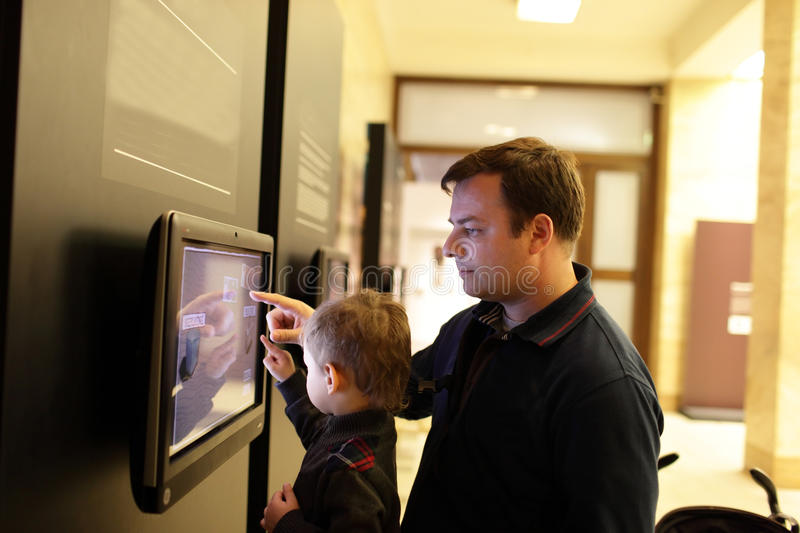 Father with son using touch screen stock photography