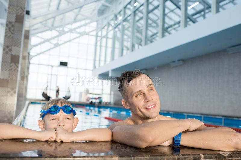 Father and son visiting swimming pool together royalty free stock photography