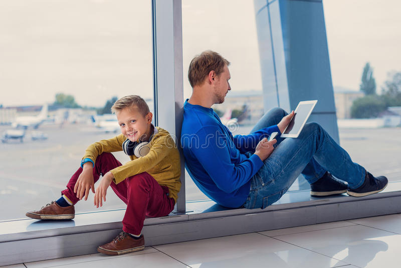 Father and son waiting to board in airport. Let is check web. Close up shot of father and his little son at airport, traveling together and waiting for their stock photo