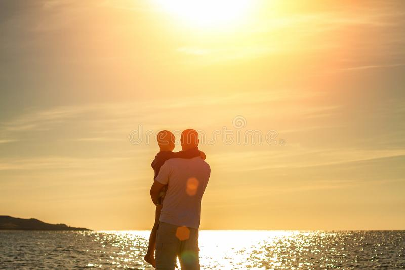 Father and son walk along the beach at sunset, summer vacation family.  stock photos