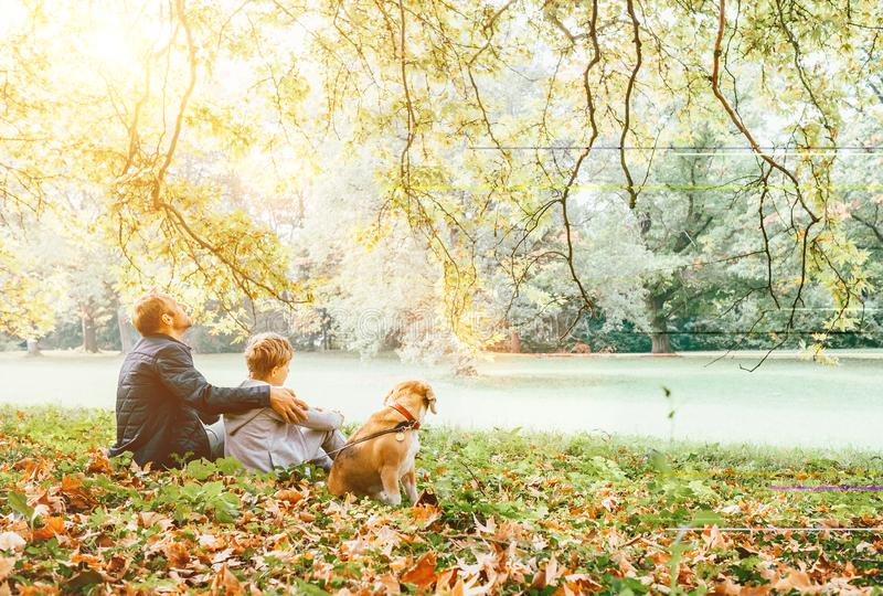 Father with son walk with beagle dog and enjoy warm autumn day royalty free stock images