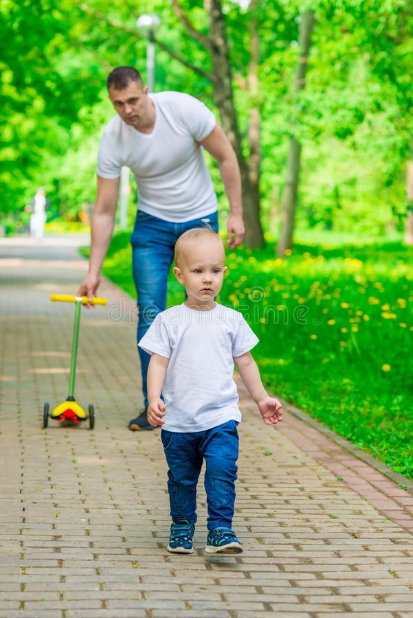Father and son on a walk in a summer park spend royalty free stock images