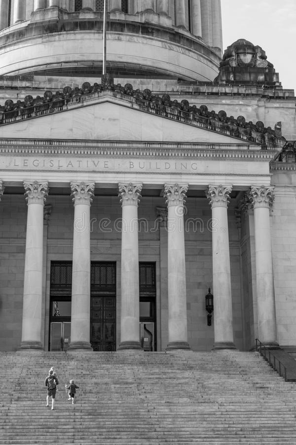 Black and white image of people walking up the steps of the Washington State Capitol building stock images