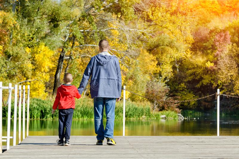 Father and son are walking along the pier. Autumn, sunny. Back v royalty free stock image