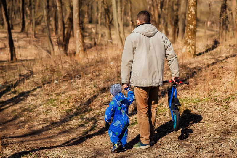 Father and son walking in early spring or autumn park / forest. Dad is holding hand of son, in other arm he is carrying run bike stock photography