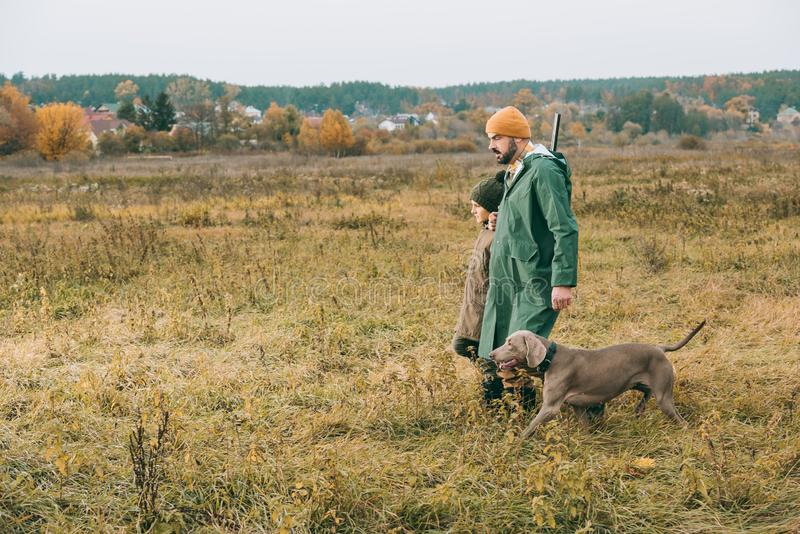 Father and son walking in a field with a dog stock photography