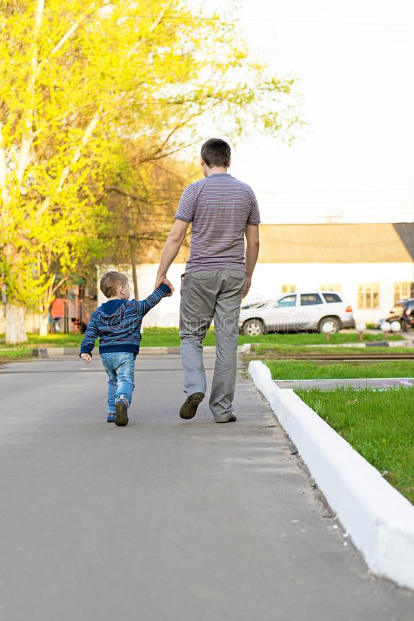 Father and son walking in an urban neighborhood royalty free stock photos