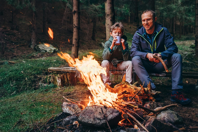 Father and son warm near campfire on forest picnic royalty free stock photography