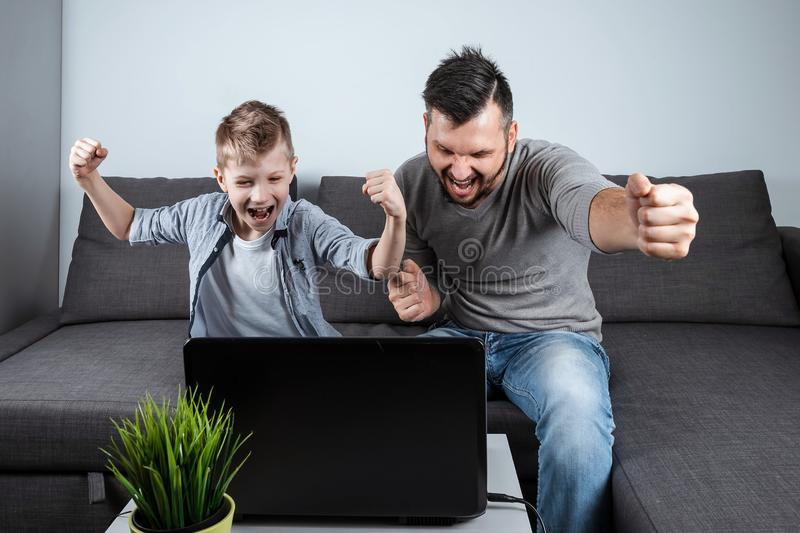 Father and son watching football in a laptop at home. Emotional man and boy, cheering favorite team. The concept of family. Father and son watching football in a stock photo