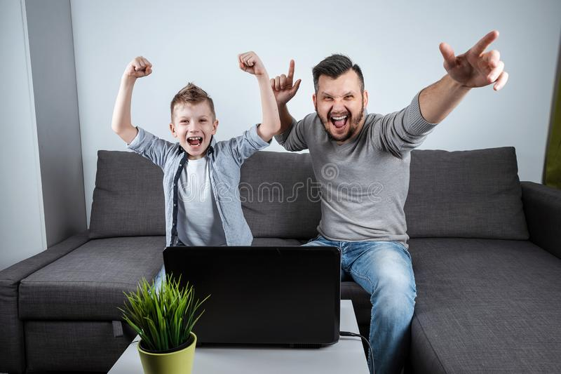 Father and son watching football in a laptop at home. Emotional man and boy, cheering favorite team. The concept of family. Father and son watching football in a stock images