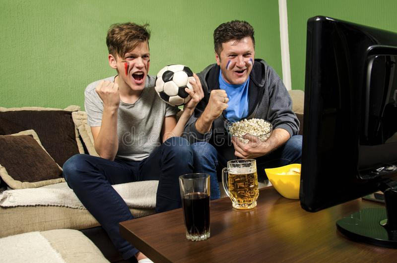 Father and son watching soccer together royalty free stock photography