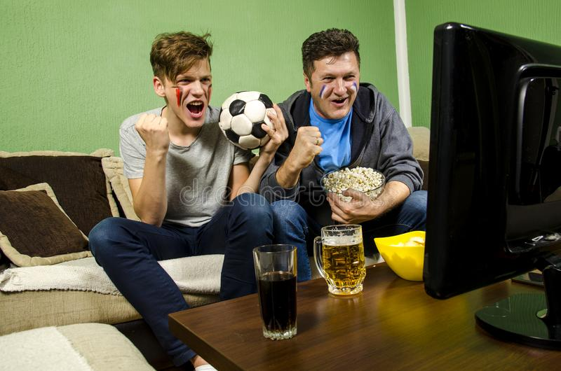 Father and son watching soccer together stock photography