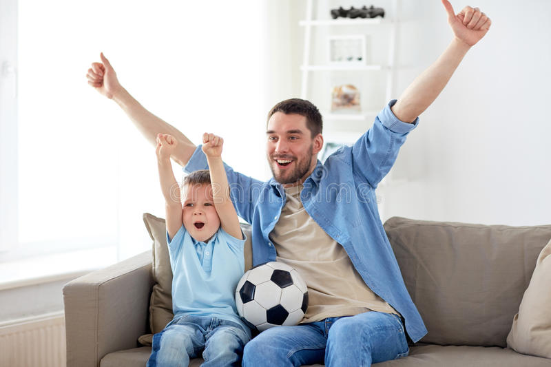 Father and son watching soccer on tv at home. Family, entertainment, sport and people concept - happy father and little son with ball watching football or soccer stock photo