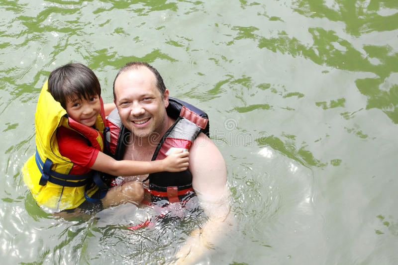 Father and son in the water. Cheerful father and son in the water wearing life vest smiling at camera royalty free stock image