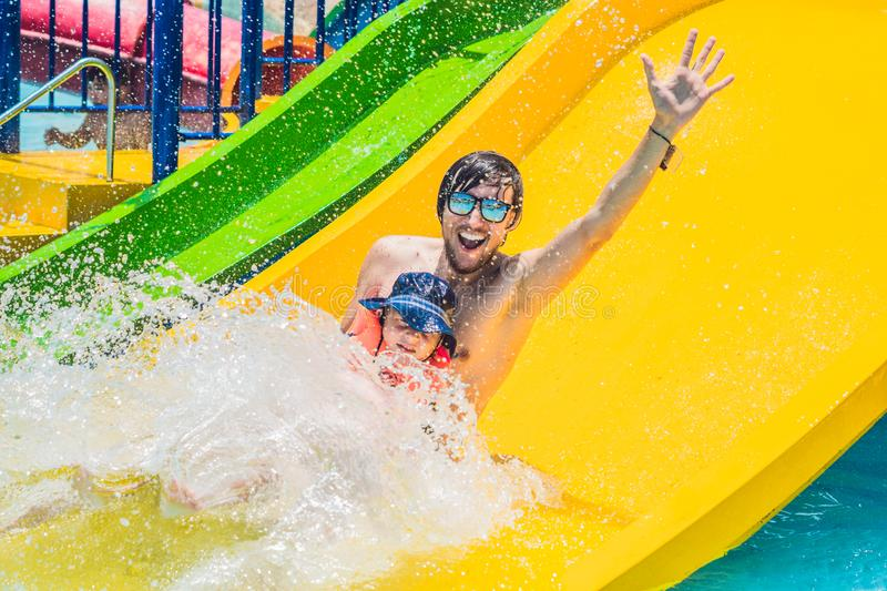 Father and son on a water slide in the water park stock image
