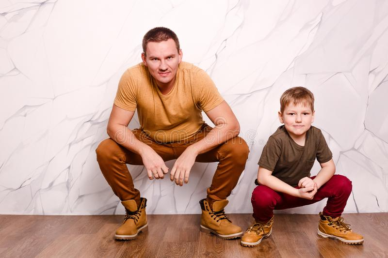 Father and son on a white background look into the camera stock photo
