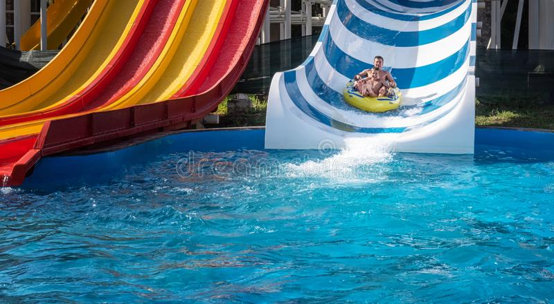 Father and son on wide striped water slide stock photos