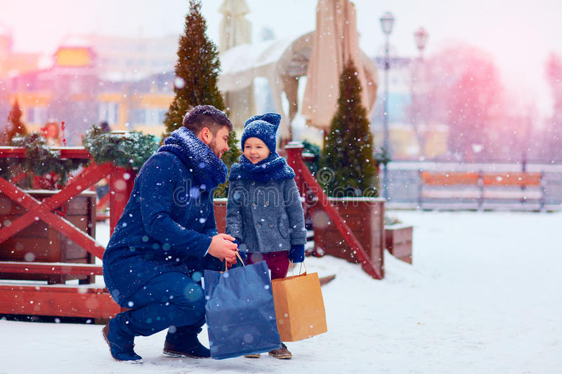 Father and son on winter shopping in city, holiday season, buying presents stock photography