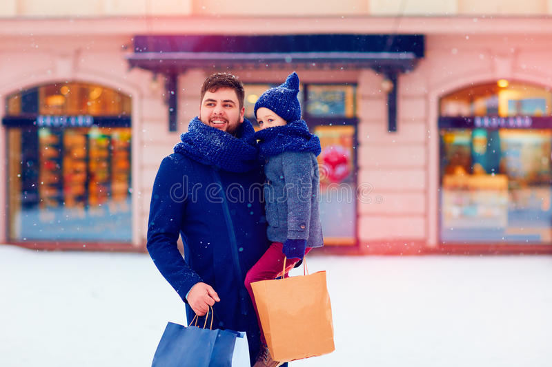 Father and son on winter shopping in city, holiday season, buying presents royalty free stock photography