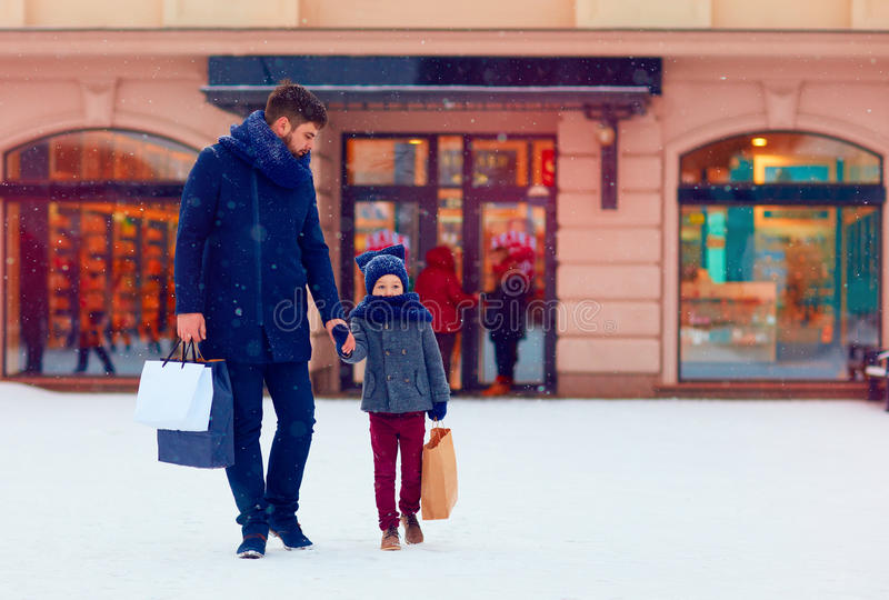 Father and son on winter shopping in city, holiday season royalty free stock photography