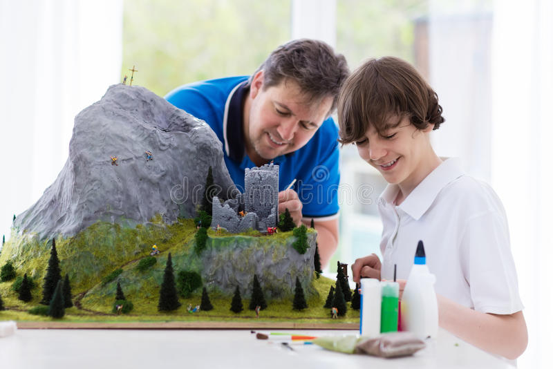 Father and son work on model building project royalty free stock photo
