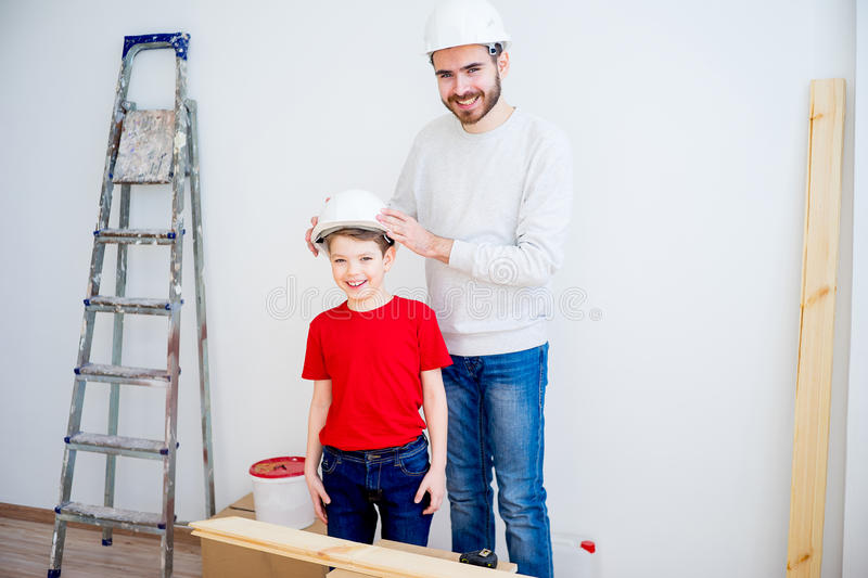 Father and son working together. Father and his son are working together at home stock images