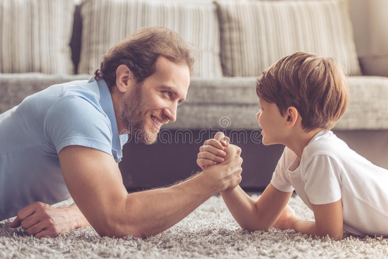 Father and son. Are wrestling and smiling while spending time together at home stock photos