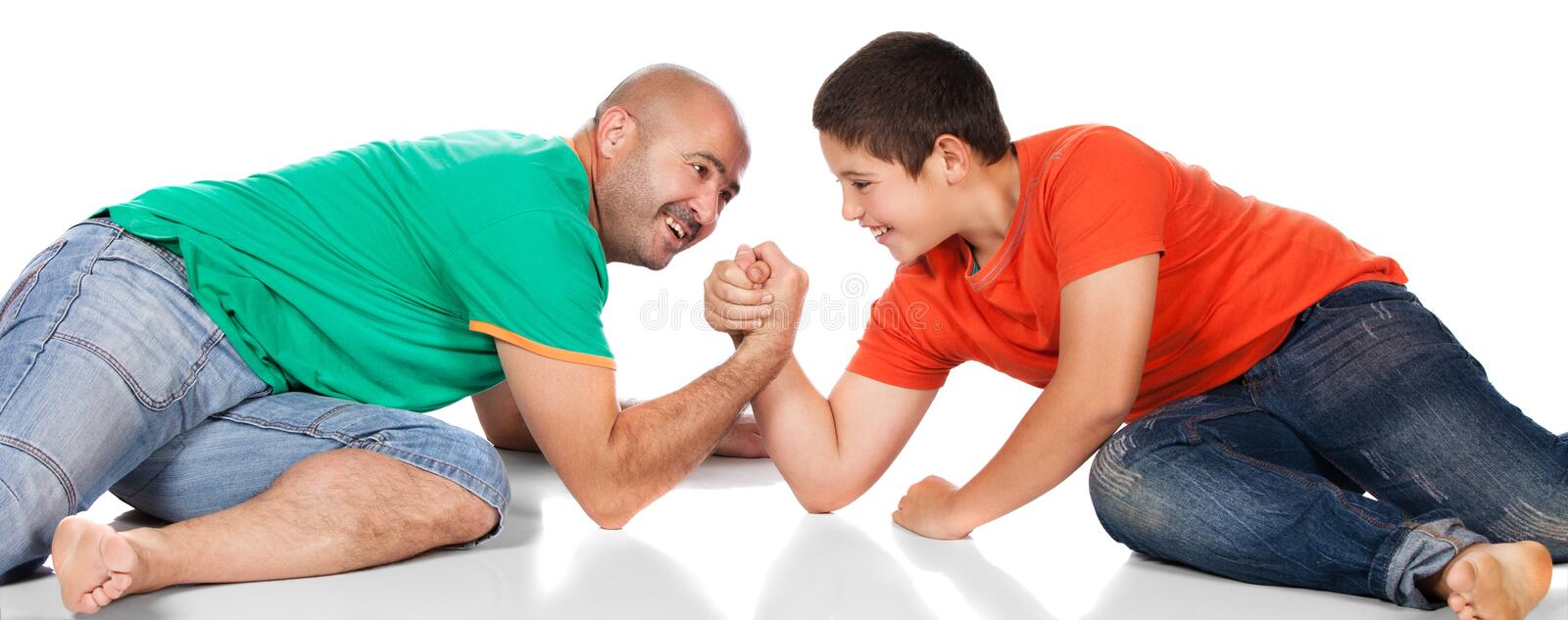 Father and son. Young caucasian boy wearing an orange t-shirt and blue jeans is playing arm wrestle with his father. The dad is wearing a green shirt royalty free stock photos