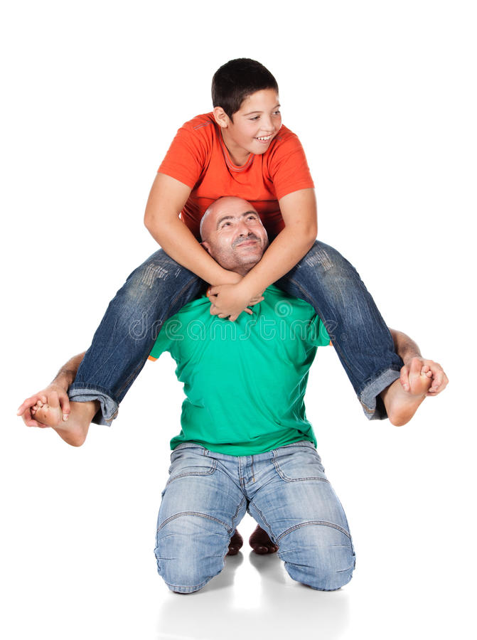 Father and son. Young caucasian boy wearing an orange t-shirt and blue jeans is playing with his father. The dad is wearing a green shirt. The boy is on the royalty free stock photography