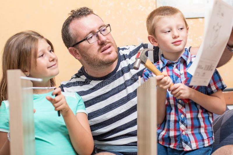 Father and sons are are building the furniture at home royalty free stock photos