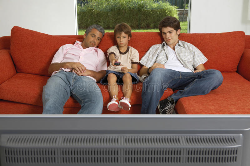 Father and sons watching TV. stock photo
