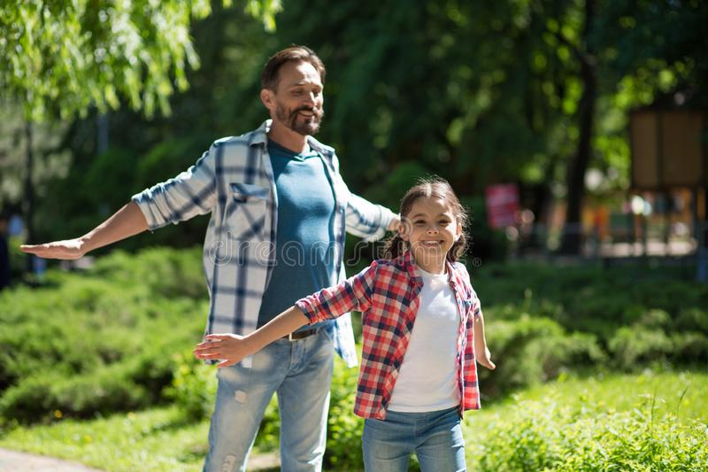 Father Spending Time with Daughter In The Park While Standind Whith Wild Opened Hands And Smiling. royalty free stock photography