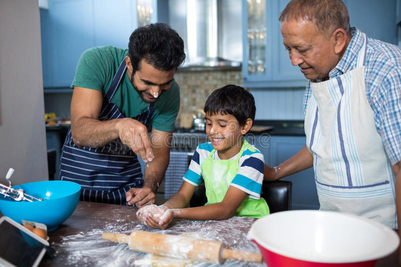 Father sprinkling flour on son hand while preparing food with grandfather. Father sprinkling flour on sons hand while preparing food with grandfather in kitchen stock image