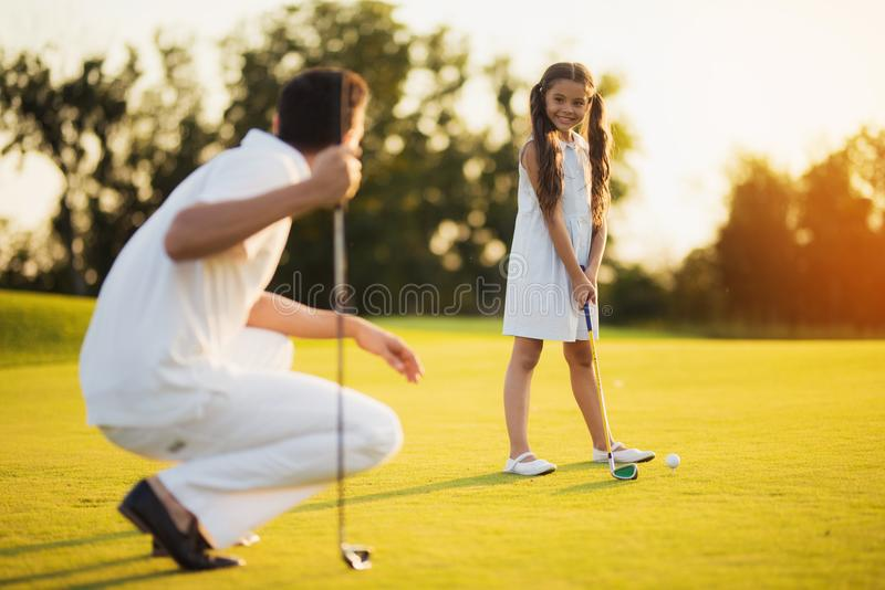 The father squats with a golf club in his hand and looks at his daughter, who looks at him and prepares to hit the ball stock image