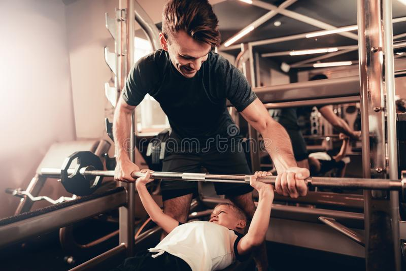 Father Support To Son While Lifting The Barbell. royalty free stock images