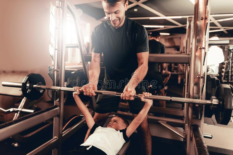 Father Support To Son While Lifting The Barbell. royalty free stock photo