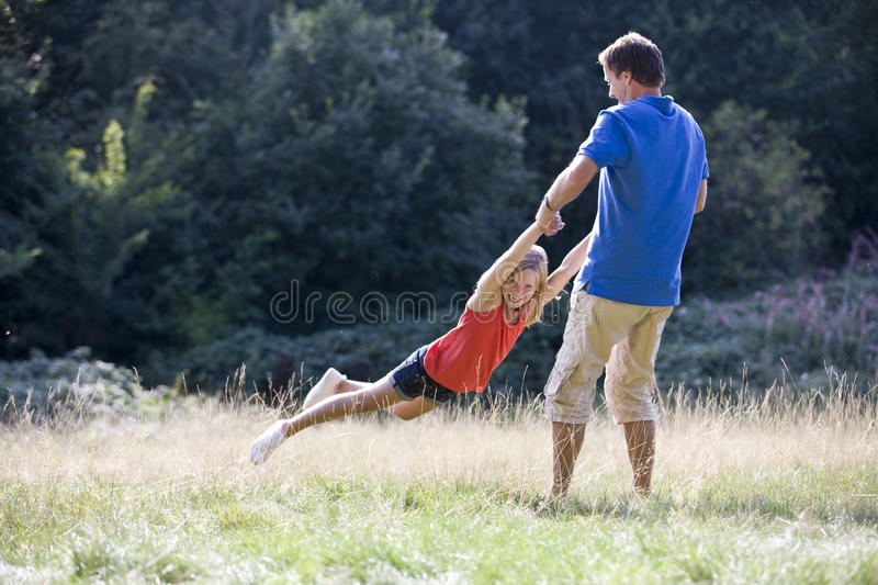 A father swinging his daughter in the park stock images