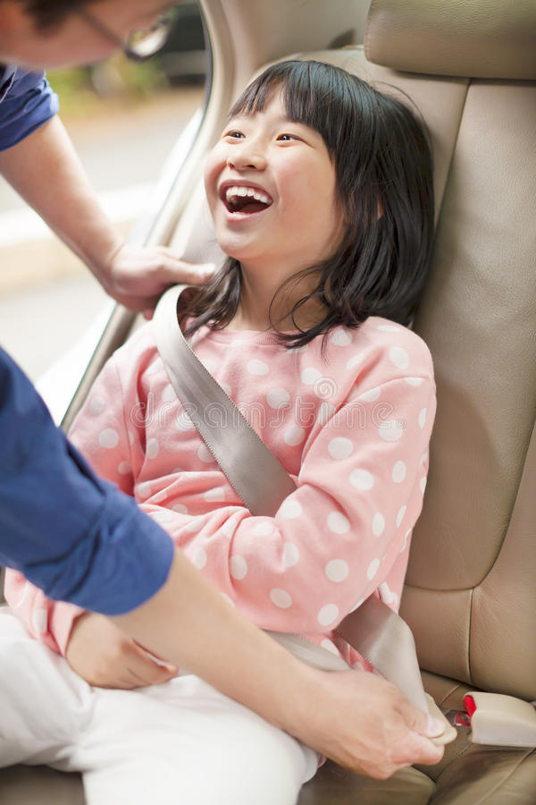 Father take care daughter to fasten a seat belt. In a car royalty free stock image