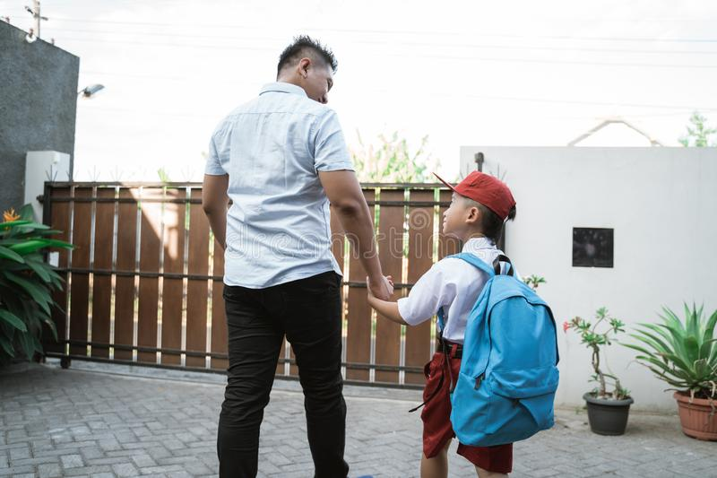 Father take his elementary student son going to school royalty free stock image