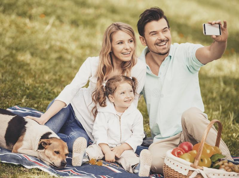 Father Takes Photo of Family on Summer Picnic. stock photography