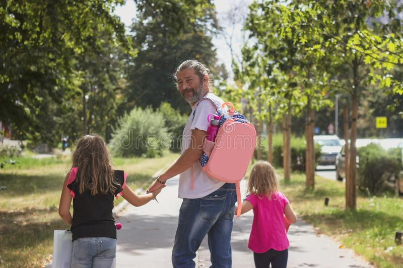 Father is taking his daughters to school, wearing kids schoolbag on his back stock images